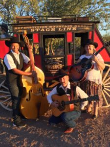 One Heart at a Time Music Group posing in front of the Superstition Mountain Museum Stagecoach