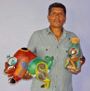 Artisan Mario holding Oaxaca Wood Carvings - Toro and a Monkey