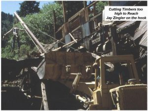 Cutting Timbers Too High to Reach (Jay Zingler suspended on the hook from a pole supported by a Front End Loader)